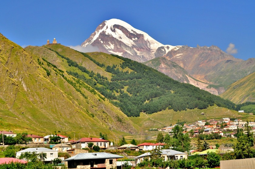 """Says one travel website: """"Climb to the Gergeti Trinity Church. This is the number 1 thing to do in Kazbegi - going to Kazbegi and not going to this Church would be… strange"""". Quite understandable, looking at this picture postcard view, isn't it? Mt. Kazbek, Gergeti Trinity Church and Gergeti village below. (© Jazzanova, via Wikimedia)"""